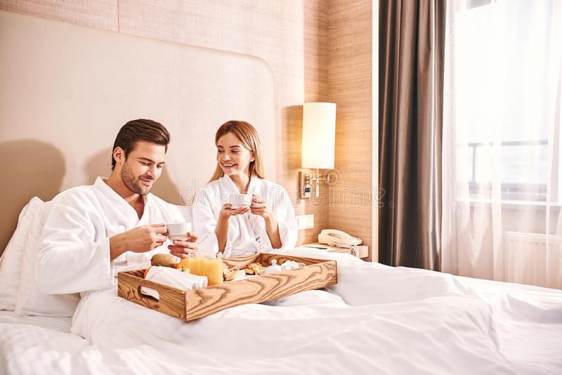 Food delivery in the room. Couple are eating in hotel room bed stock image
