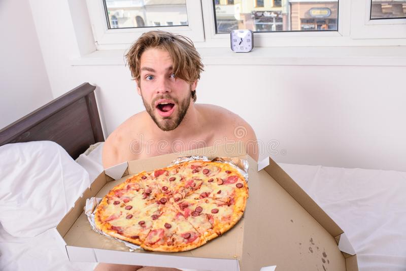 Food delivery service. Man bearded handsome guy eating cheesy food for breakfast in bed. Man likes pizza for breakfast stock photo