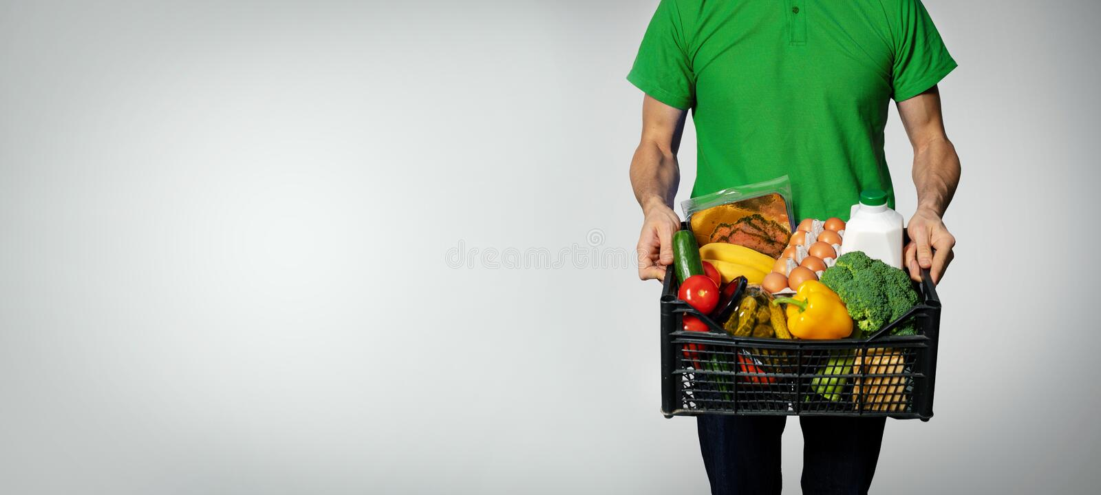 Food delivery service - man with groceries box in hands. Food delivery service - man with groceries box on gray background with copy space stock image