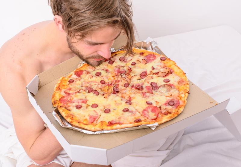 Food delivery service. Man likes pizza for breakfast. Bachelors nutrition. Man bearded handsome guy eating cheesy food. For breakfast in bed. Guy holds pizza stock photo