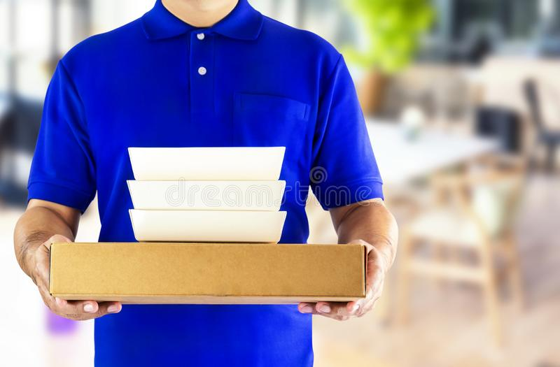 Food delivery service or order food online. Delivery man in blue. Uniform with hand holding food packaging container on the gray background stock images