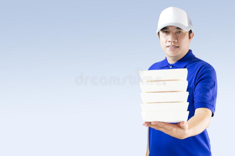 Food delivery service or order food online. Delivery man in blue uniform with hand holding paper packaging container fast food for. Take away home isolated on stock photo