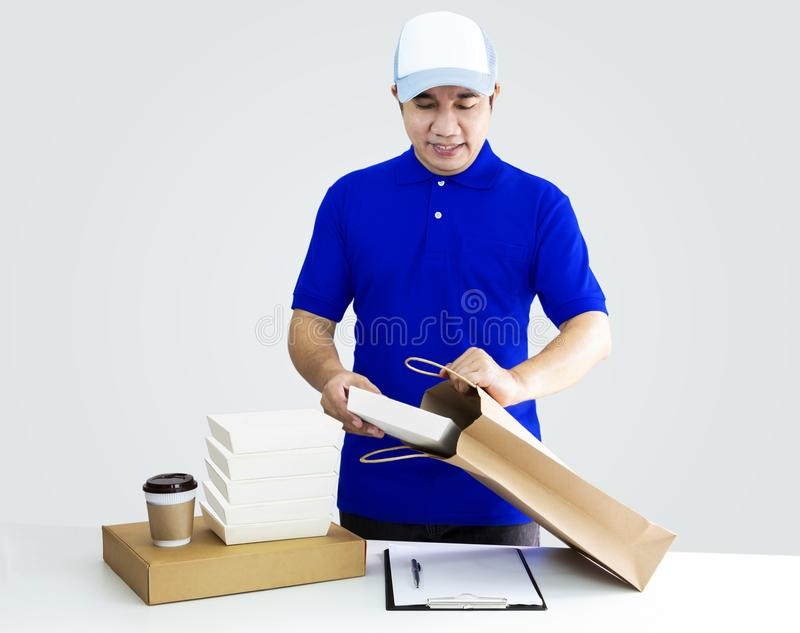 Food delivery service or order food online. Man putting in takeout food container into paper bag with coffee cup in holder and pa. Ckaging on gray background stock images