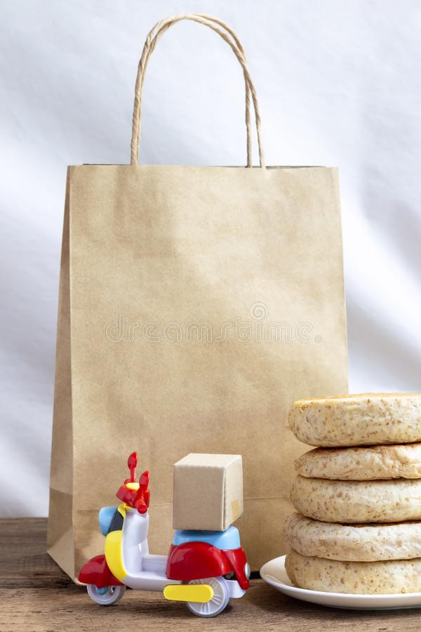 Food delivery service for order online concept. Business express service delivery for food by motorcycle at home. Paper bag and. Bakery on wooden background royalty free stock photos