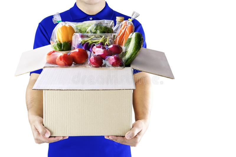 Food delivery service for order online grocery shopping concept. Delivery man in blue uniform hand holding paper box package. Express delivery service fast stock photo