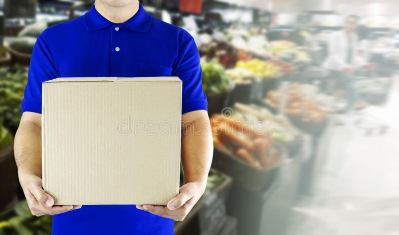 Food delivery service for order online grocery shopping concept. Delivery man in blue uniform hand holding paper box package. Express delivery service fast royalty free stock images