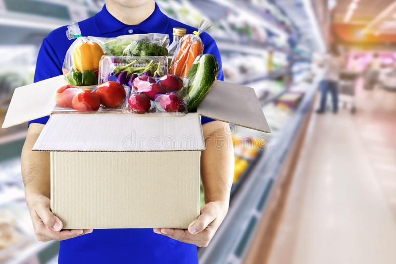 Food delivery service for order online grocery shopping concept. Delivery man in blue uniform hand holding paper box package. Express delivery service fast stock image