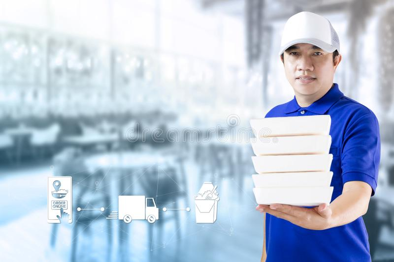 Food delivery service or order food online. Delivery man hand holding fast food packaging in blue uniform and icon symbol media on. Restaurant background stock images