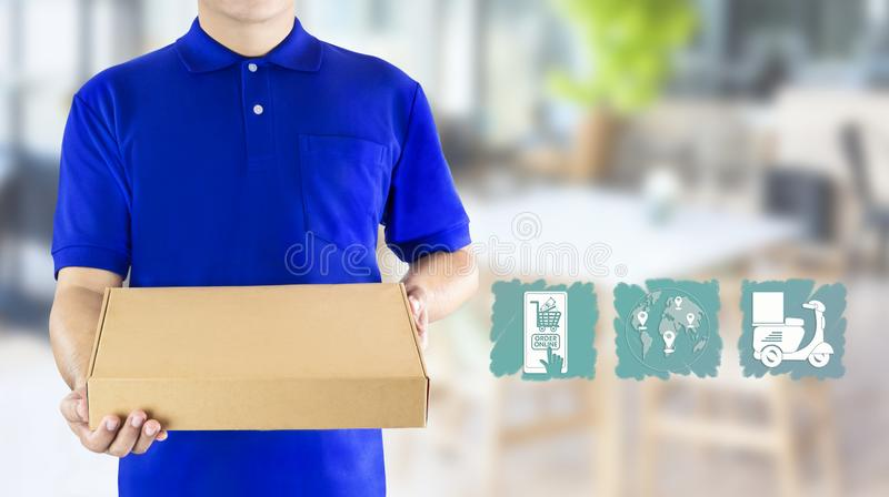 Food delivery service or order food online. Delivery man hand holding fast food packaging in blue uniform and icon symbol media on. Restaurant background stock photo