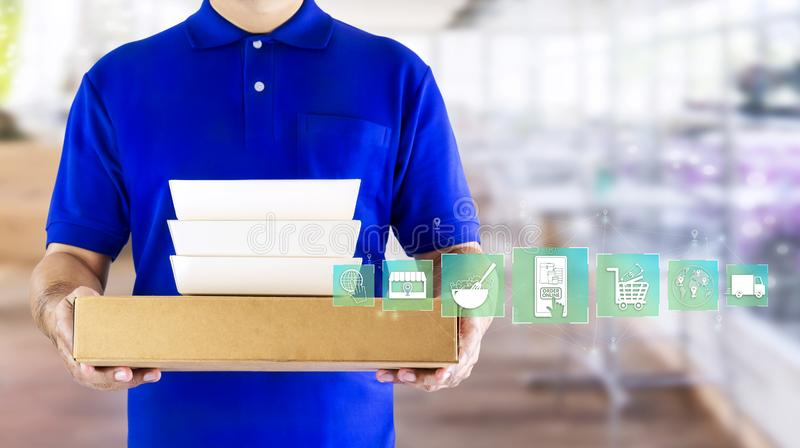 Food delivery service or order food online. Delivery man hand holding fast food packaging in blue uniform and icon symbol media on. Restaurant background royalty free stock photography