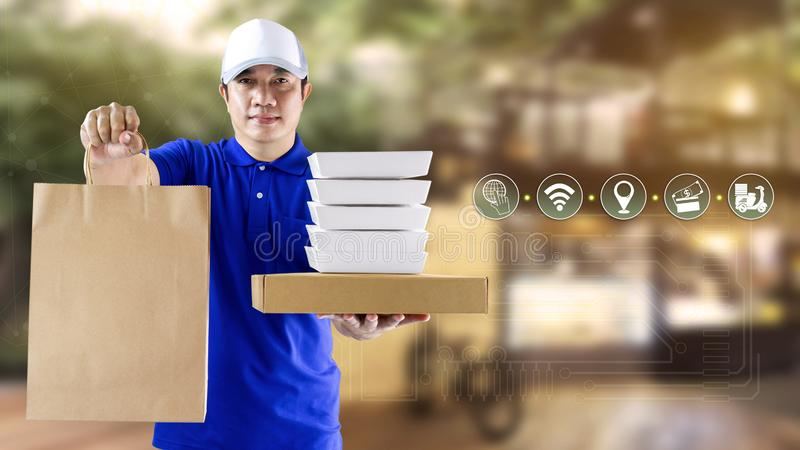 Food delivery service for order online shopping concept and icon media symbol. Delivery man in blue uniform hand holding paper bag. And box packaging for fast royalty free stock image
