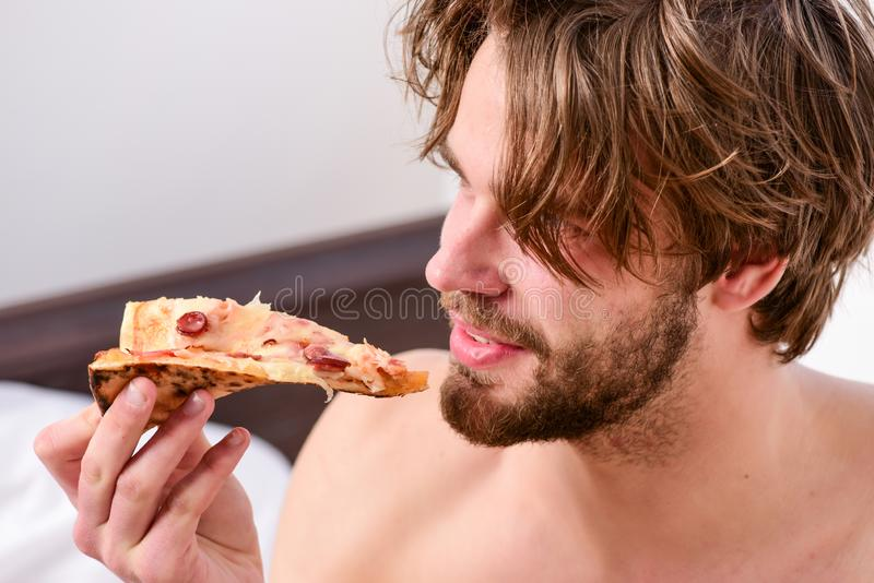 Food delivery service. man eat pizza lying on bed. Young man resting at home with a nude and a pizza. Eating pizza royalty free stock images
