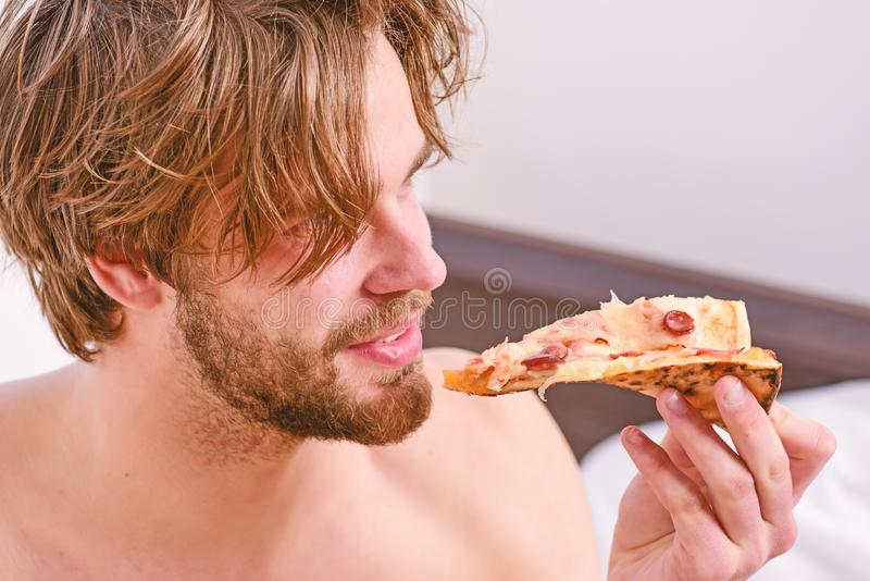 Food delivery service. Sexy man eat pizza lying on bed. Young man resting at home with a nude and a pizza. Eating pizza stock images