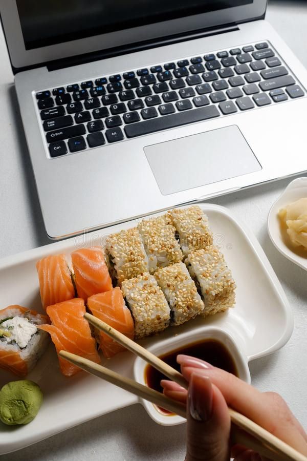 Food delivery service sushi rolls online order. Food delivery service. Sushi rolls assortment fresh from a restaurant. Laptop online meal order royalty free stock photography