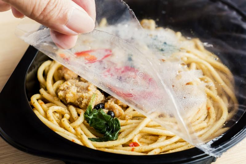 Food Delivery service: Woman hands holding open cling wrap and take out food in plastic boxes on wood background. concept online royalty free stock photos