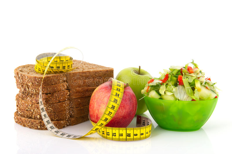 Food for diet. Healthy food for diet as bread fruit and vegetables with measurement tape stock images