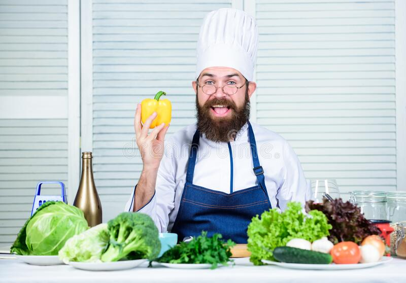 Food for dinner. Chef man in hat. Secret taste recipe. Dieting and organic food, vitamin. Bearded man cook in kitchen royalty free stock image