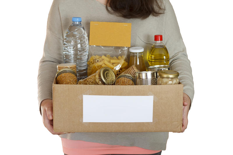 Food in a donation box. Volunteer holding food in a donation cardboard box, isolated in a white background stock photo