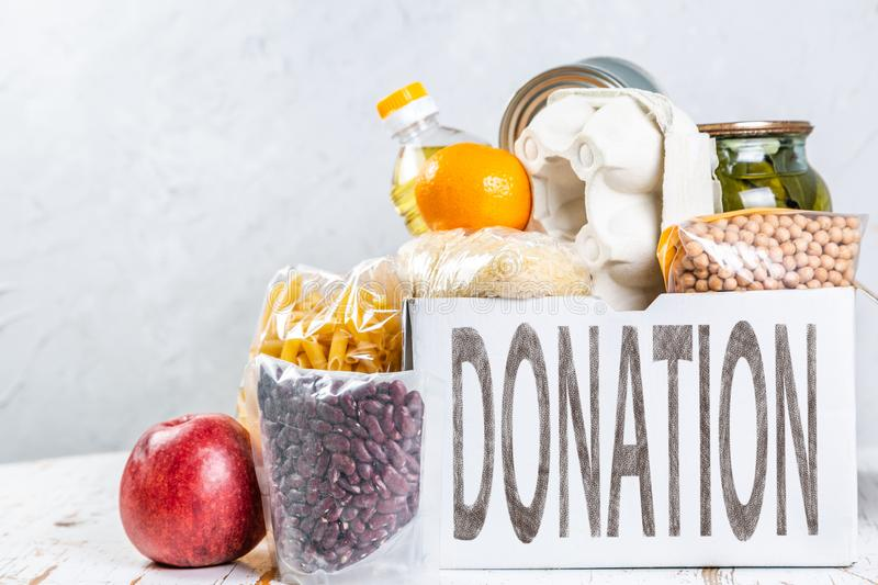 Food donations in box in kitchen background royalty free stock photo
