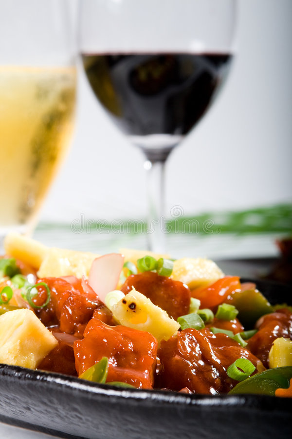 Food and drink. Chinese food sweet sour pork and red wine and beer royalty free stock photo