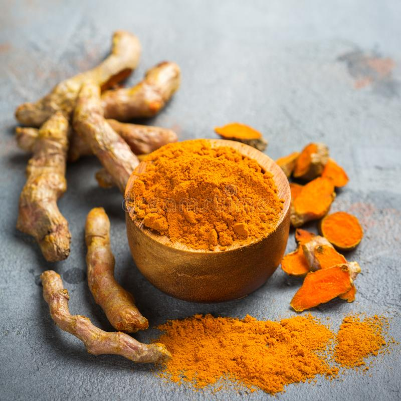 Raw turmeric root curcuma longa powder. Food and drink, diet nutrition, health care concept. Raw organic orange turmeric root and powder, curcuma longa on a royalty free stock photography