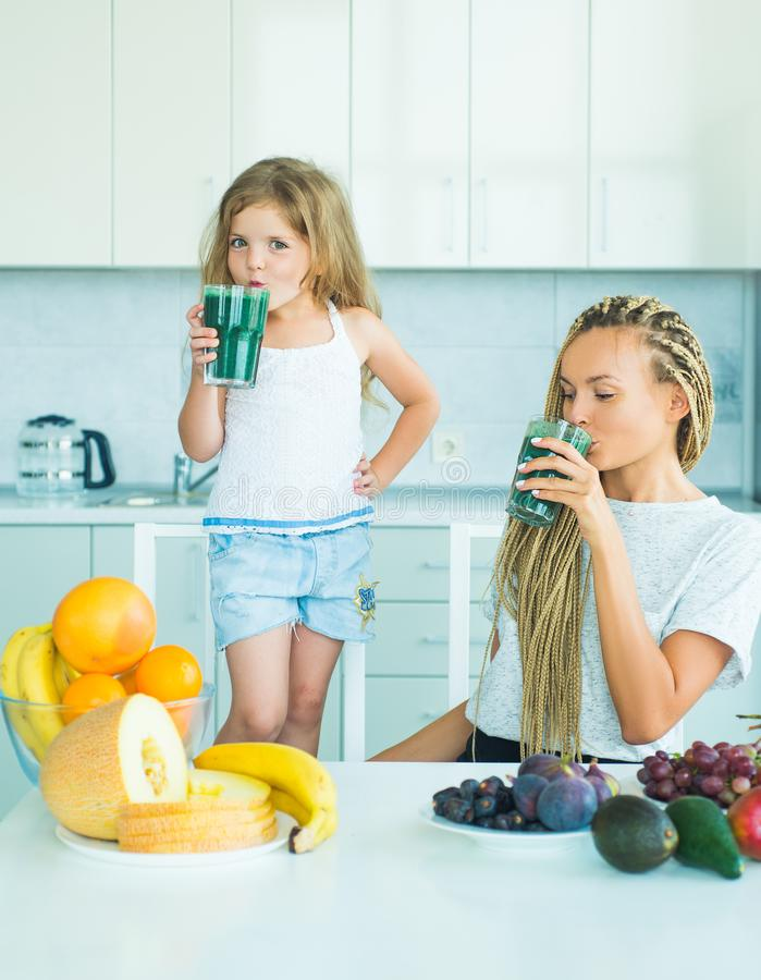 Food and Drink for kids. Mother and daughter blending cocktail with fruits. Vegan concept. Healthy summer drink. Natural royalty free stock photos