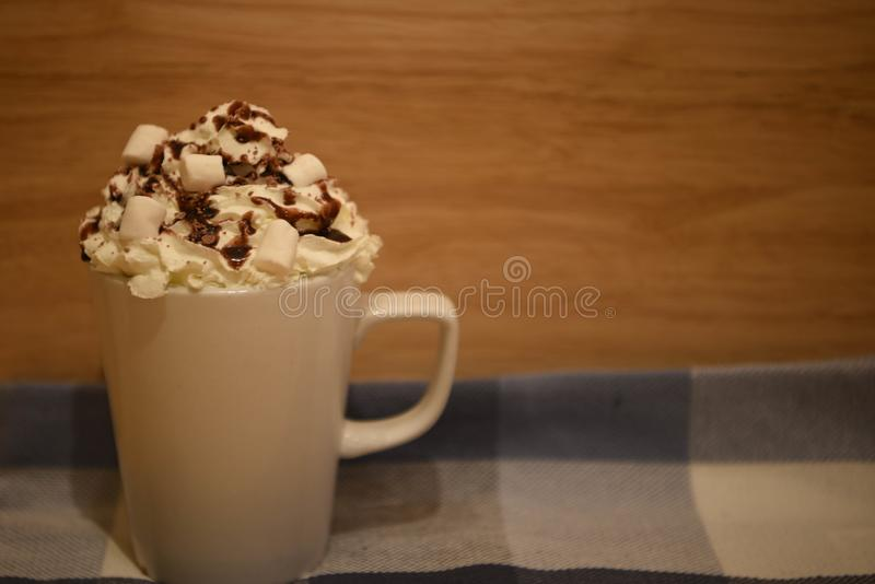 Close up food photography image of hot chocolate drink in a mug with cream sauce and marshmallows on a blue cloth background royalty free stock photo