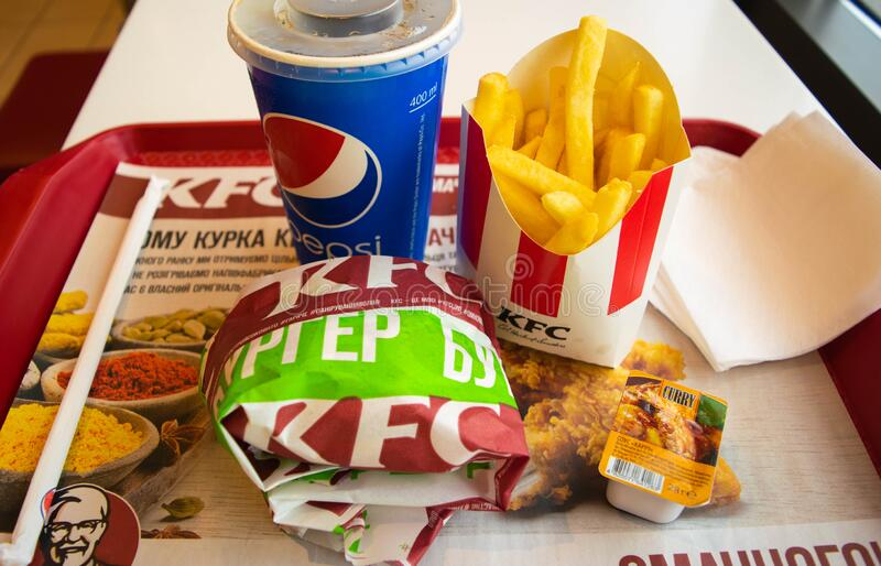 Food and drink in a popular fast food restaurant KFC. Potato fries, Pepsi and burger with curry sauce stock photography