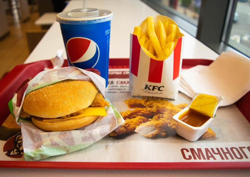 Food and drink in a popular fast food restaurant KFC. Potato fries, Pepsi and burger with curry sauce stock images