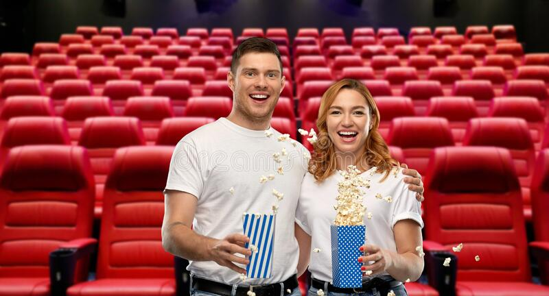 Happy couple in t-shirts with popcorn at cinema stock photos
