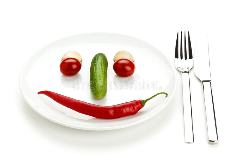 Food face. From cherry tomatoes, chili pepper, cucumber and garlic cloves on plate with cutlery, isolated on white stock photo
