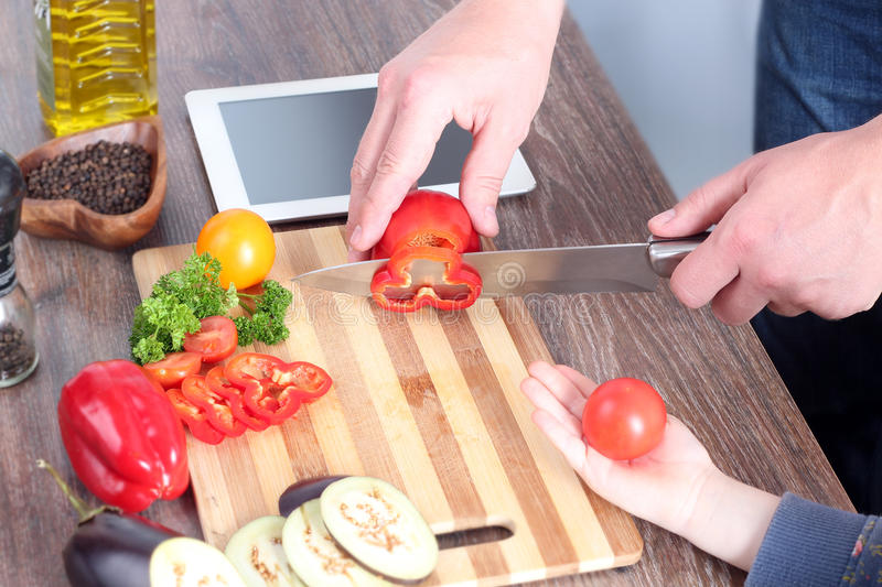 Food, family, cooking and people concept - girl giving tomato to the father. Man chopping paprika. stock photos