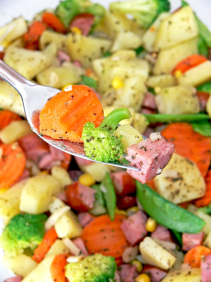 Food on fork. Close up of the steel fork with pieces of food stock images