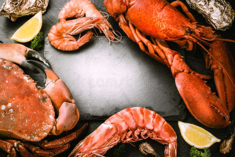 Food frame with crustacean for dinner. Lobster, crab, jumbo shrimps and oysters. On dark background with copyspace stock photos