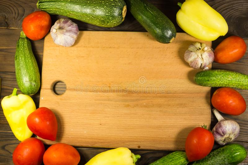 Food frame with fresh organic vegetables. Tomatoes, cucumbers, pepper, zucchini and garlic on wooden kitchen table. Healthy food concept royalty free stock image