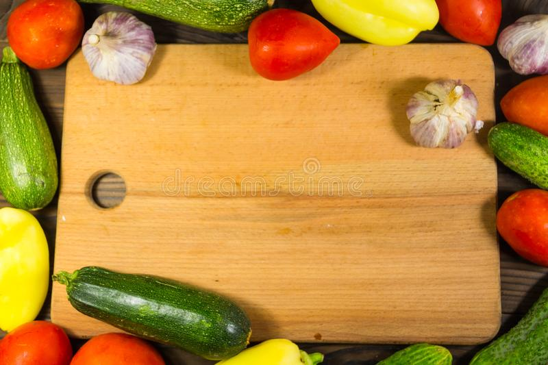 Food frame with fresh organic vegetables. Tomatoes, cucumbers, pepper, zucchini and garlic on wooden kitchen table. Healthy food concept royalty free stock images