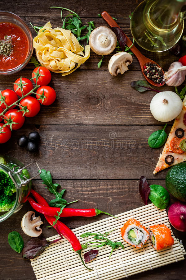 Food frame made of vegetables, pizza, sushi rolls, tomato, pasta, olives and sauce on wooden background. Concept for menu. Flat la royalty free stock photos