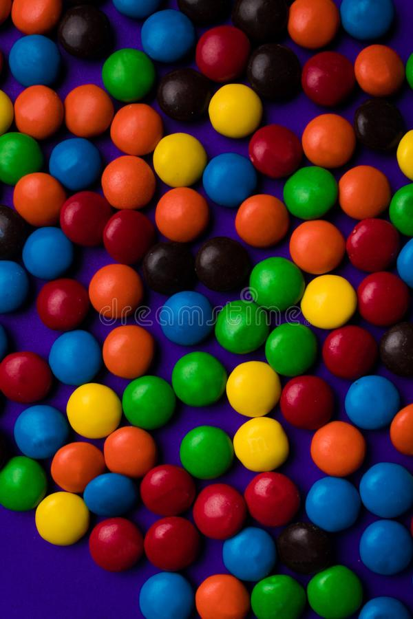 Frame of multicolor candy with a free space on a purple background. stock photos