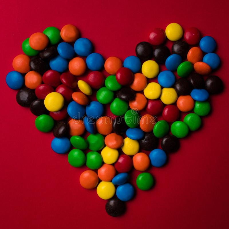 Multicolored candy with the shape of a heart on a red background. royalty free stock images