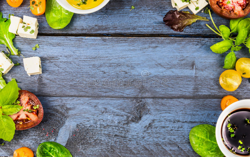 Food frame with salad ingredients: oil, vinegar, tomatoes, basil and cheese on blue rustic wooden background. Top view, horizontal stock photo
