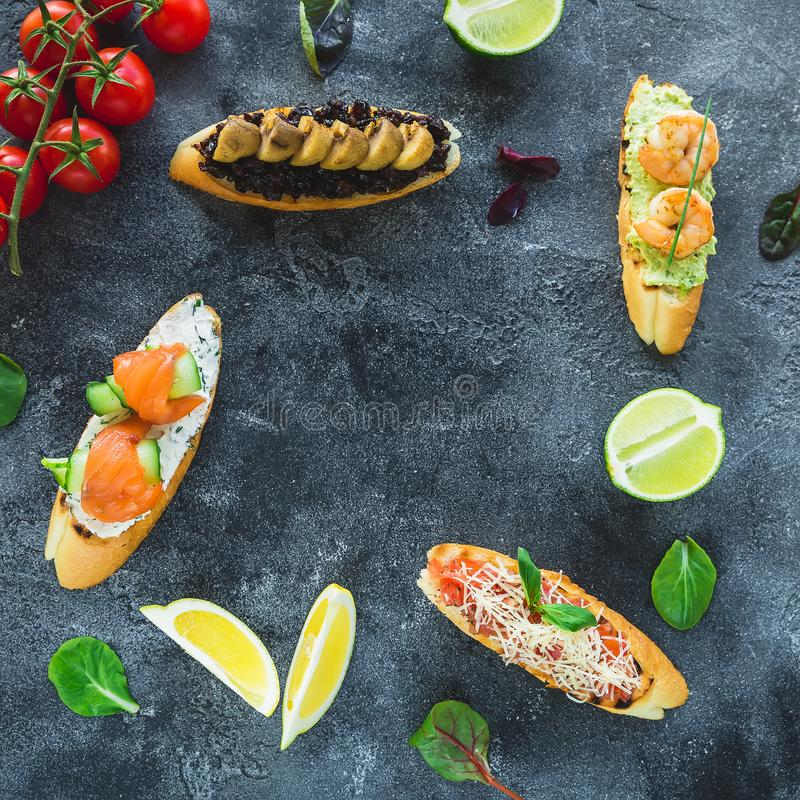 Food frame of sandwiches with prawn, salmon, mushroom and limes on dark background. Restaurant food royalty free stock photo