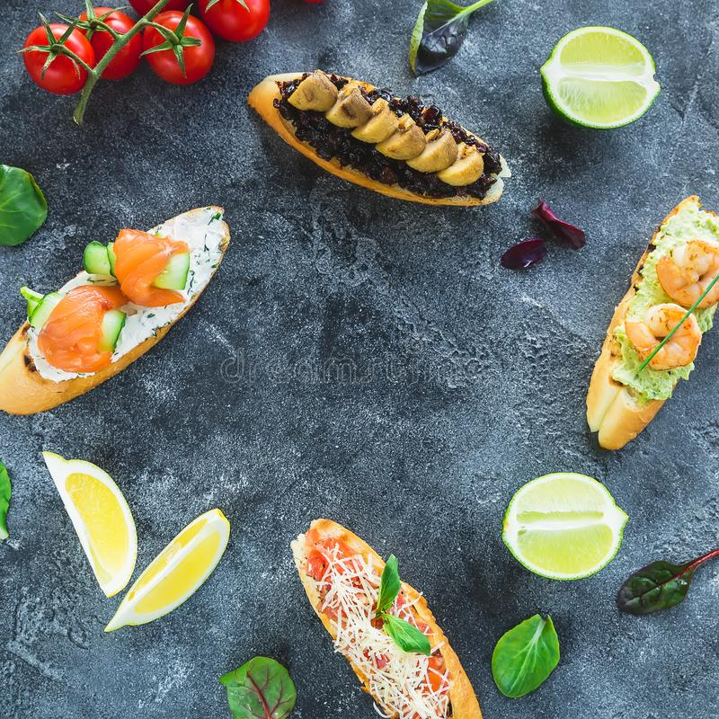 Food frame of tasty sandwiches with prawn, salmon, mushroom and limes on dark background. Restaurant food royalty free stock photos