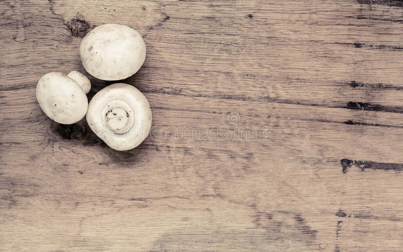 Food. Fresh white mushrooms champigonons. Vegetarian food. Fresh white mushrooms champigonons on wooden kitchen table as background stock image