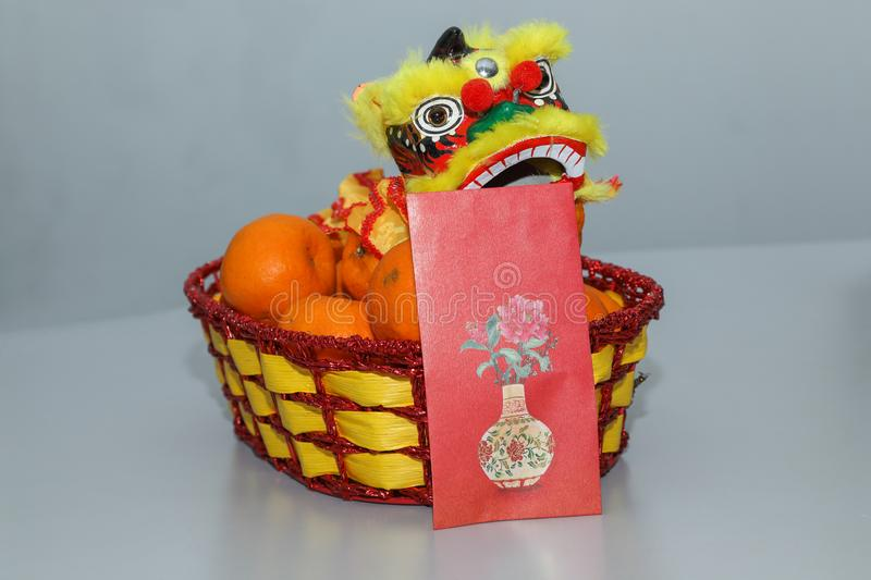 Chinese New Year orange fruit basket with beautiful Chinese dragon and angpao, front view close up Spring festival royalty free stock image