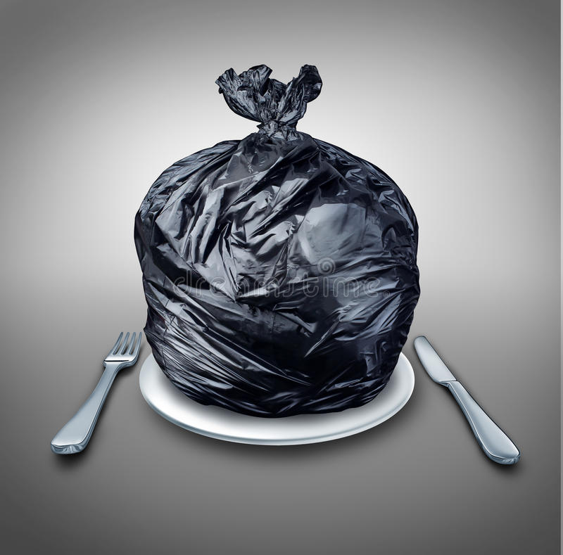 Food Garbage. And poor nutrition concept as a table setting with a black plastic garbage bag on a dinner plate with a knife and fork as a metaphor for a bad