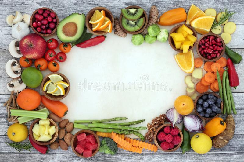 Food for Good Health. And fitness background border with fresh vegetables, fruit, herbs, spices and nuts on parchment and rustic wood. Super foods concept high stock photo