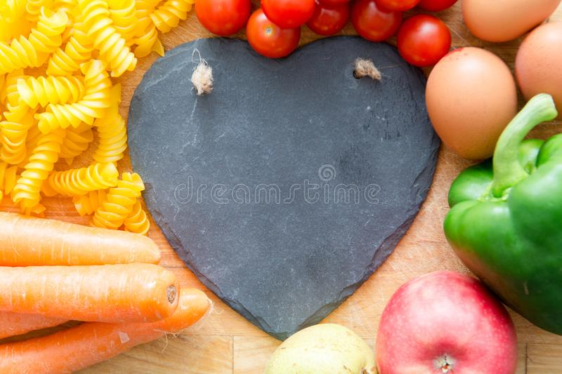 Food groups, natural healthy fruit and vegatables with a heart s. Food groups, natural healthy fruit and vegetables with a heart shape chalk board royalty free stock photography