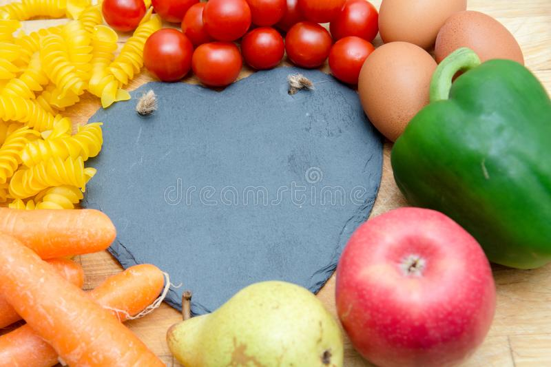 Food groups, natural healthy fruit and vegatables with a heart s. Food groups, natural healthy fruit and vegetables with a heart shape chalk board royalty free stock image