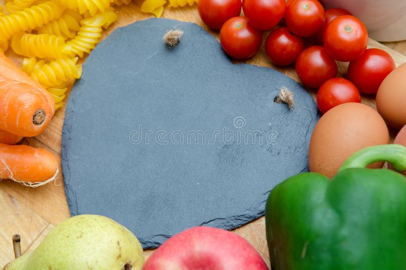 Food groups, natural healthy fruit and vegatables with a heart s. Food groups, natural healthy fruit and vegetables with a heart shape chalk board royalty free stock photo