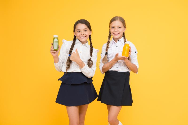Food habits. little girls hold healthy juice or yoghurt. lunch time on school break. pupils on yellow background royalty free stock photography